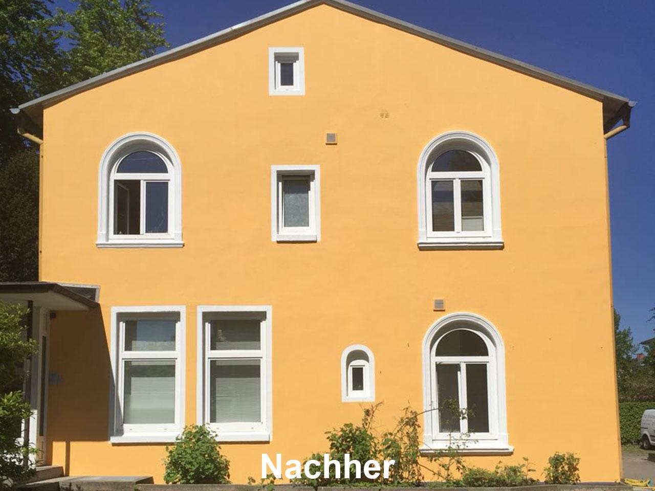 Frontansicht eine gelben Hauses nach Fassadenrenovierung