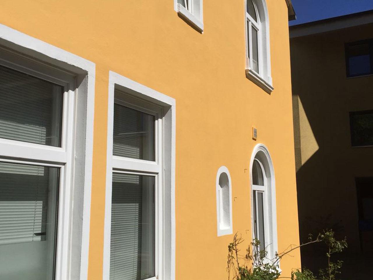 Schräge Ansicht auf gelbes Haus nach Fassadenrenovierung