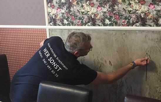 Mitarbeiter von Malereibetrieb Sven Brockmann zeichnet Betonotpik an Wand