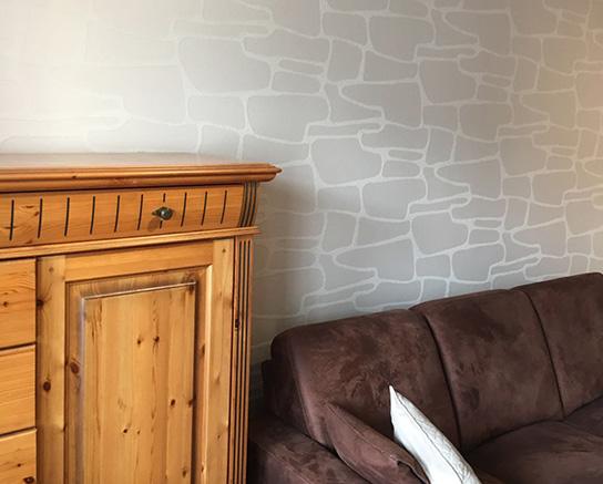 Kommode und Sofa vor Wand mit Mustertapete