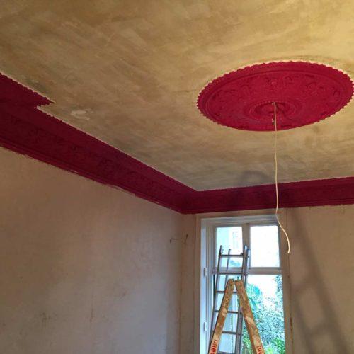 Vorherbild einer Decke mit rotem Stuck in einer Albauwohnung während der Malerarbeiten