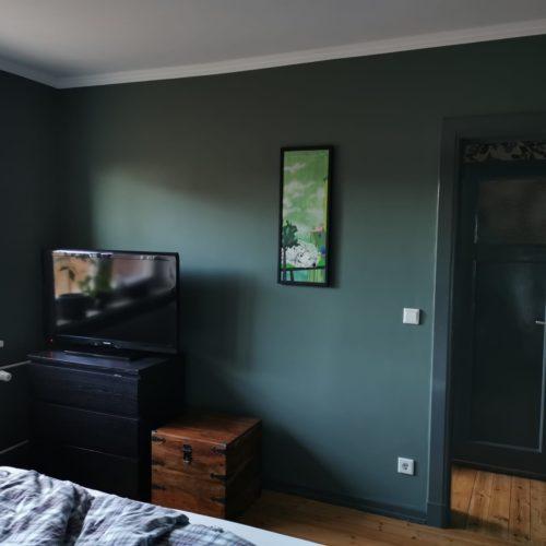 Nachherbild dunkelgrün gestrichenes Schlafzimmer mit Blick auf Fernsehwand