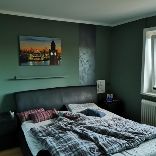Nachherbild eines dunkelgrün gestrichenes Schlafzimmer mit Blick auf Bett