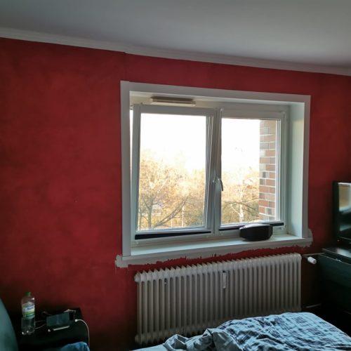 Vorherbild eines rot gestrichenen Schlafzimmers mit Blick auf Fenster