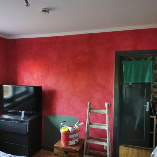 Vorherbild eines rot gestrichenen Schlafzimmers mit Blick auf TV-Wand