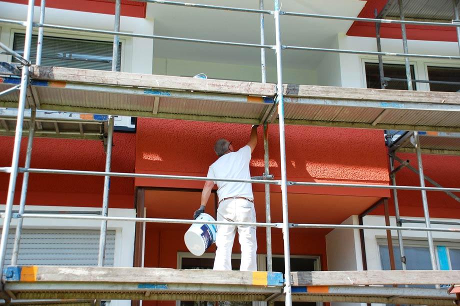 Maler auf einem Gerüst an Hausfassade als Symbolbild für Malerarbeiten und Fassadenrenovierung in Hamburg